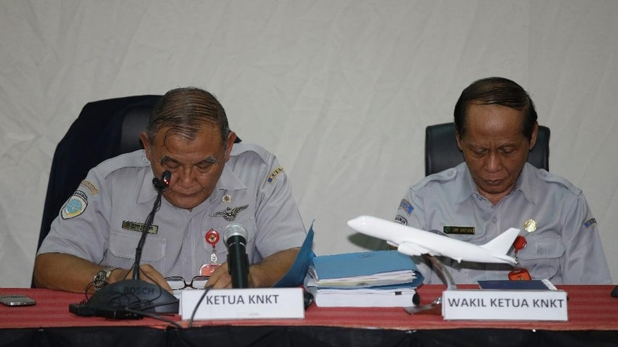 Indonesian National Transportation Safety Committee (KNKT) chief Tatang Kurniadi, left, and his deputy Sri Untung observe a moment of silence for the victims of AirAsia Flight 8501 prior to a press conference in Jakarta, Indonesia, Thursday, Jan. 29, 2015. Indonesian investigators announced Thursday the co-pilot of the crashed AirAsia jet was in controls when he struggled to recover the aircraft as stall warnings sounded. (AP Photo/Dita Alangkara)