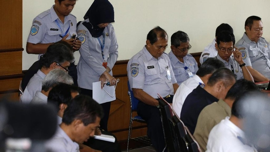 Indonesian Transportation Ministry officials observe a moment of silence for the victims of AirAsia Flight 8501 prior to a press conference in Jakarta, Indonesia, Thursday, Jan. 29, 2015. Indonesian investigators announced Thursday the co-pilot of the crashed AirAsia jet was in controls when he struggled to recover the aircraft as stall warnings sounded. (AP Photo/Dita Alangkara)