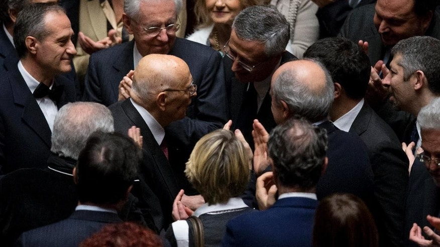 Former Italian President Giorgio Napolitano, center, is greeted by lawmakers as he arrives at the lower chamber  to attend the voting session electing the new Italian President in Rome, Thursday, Jan. 29, 2015. Lawmakers cast ballots Thursday for a new Italian president in a vote testing Premier Matteo Renzi's ability to rally his divided party behind his reform agenda and a single candidate who is also agreeable to ex-Premier Silvio Berlusconi. Polling was expected to last at least until Friday or Saturday since the threshold slips from a two-thirds majority to a simple majority after three rounds of voting. (AP Photo/Alessandra Tarantino)