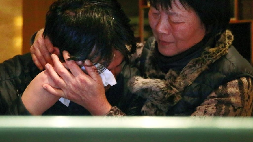 "Jiang Hui, left, is comforted by Dai Shuqin, both are relatives of passengers onboard the Malaysia Airlines Flight 370 that went missing on March 8, 2014, after watching a pre-recorded message broadcast on Malaysian television by Malaysia's Civil Aviation Authority from a laptop computer in Beijing, Thursday, Jan. 29, 2015. Malaysia's Civil Aviation Authority on Thursday officially declared the crash of Flight 370 an accident, fulfilling a legal obligation that will allow efforts to proceed with compensation claims. Malaysia civil aviation chief Azharuddin Abdul Rahman said that the search for the Malaysia Airlines jet that disappeared on the way from Kuala Lumpur to Beijing, ""remains a priority."" (AP Photo/Andy Wong)"