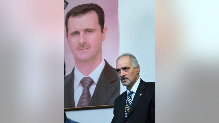 Bashar Jaafari, who represented the Syrian government in Moscow consultations between Syrian government and opposition representatives, leaves a news conference in Moscow Thursday, Jan. 29, 2015, with a portrait of Syria's President Bashar Assad is in the background. Jaafari said disagreement between opposition members made any agreement difficult, but added that there was tentative agreement to continue consultations. (AP Photo/Alexander Zemlianichenko)