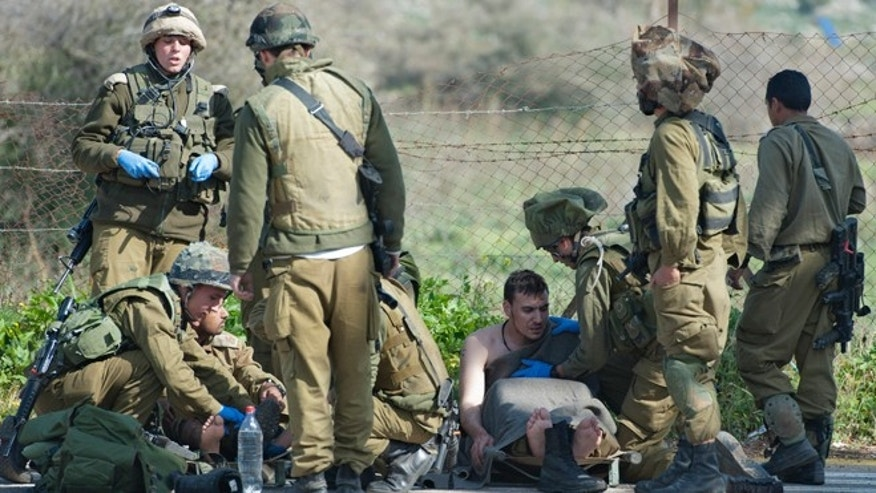Jan. 28, 2015: Israeli soldiers treat a wounded soldier near the Israel-Lebanon border. A missile fired by the Lebanese Hezbollah group struck an Israeli military convoy on Wednesday, killing two soldiers in an apparent retaliation for a deadly airstrike attributed to Israel that killed many Hezbollah fighters in Syria earlier this month. The violence was the deadliest Hezbollah attack on Israel since a 2006 war between the two sides.