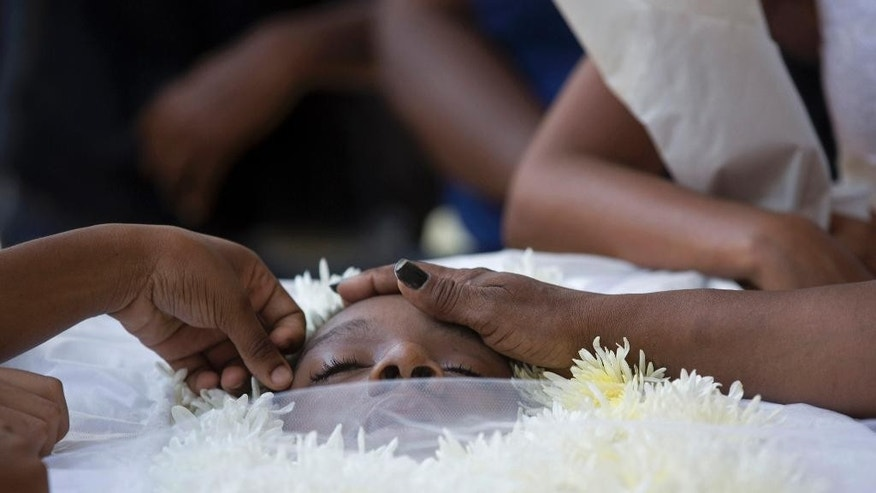 In this Jan. 27, 2015 photo, relatives and friends touch the face of Adriene Nascimento who was killed by a stray bullet, during her funeral at the Sao Joao Batista cemetery in Rio de Janeiro, Brazil. Nascimento, a 21-year-old mother of two, died holding a child in her lap when a stray bullet came as police and gang members traded fire nearby. (AP Photo/Silvia Izquierdo)