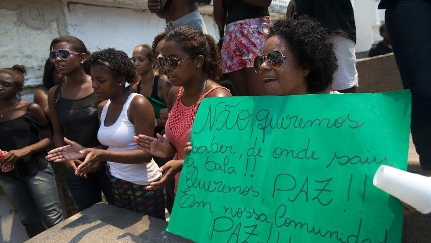 "In this Jan. 27, 2015 photo, a woman at the Sao Joao Batista cemetery holds a sign that reads in Portuguese ""We don't want to know where the bullets came from. We want peace in our community, peace,"" during the burial of Adriene Nascimento who was killed by a stray bullet in Rio de Janeiro, Brazil. Community leaders are complaining that a police crackdown on criminal gangs is provoking heavy-powered gun battles that are catching innocent bystanders in the violence. (AP Photo/Silvia Izquierdo)"