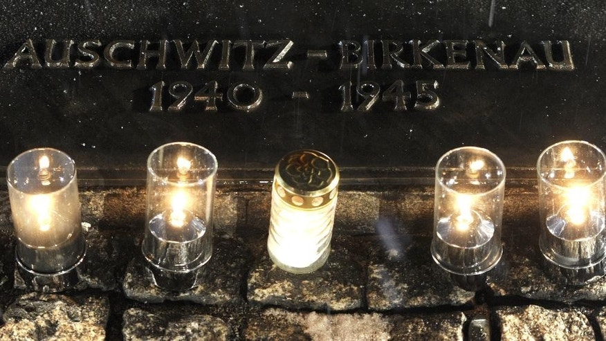Candles burn by a memorial plaque at the Birkenau Nazi death camp in Oswiecim, Poland, Tuesday, Jan. 27, 2015, after the official remembrance ceremony. About 300 survivors gathered with leaders from around the world to remember the 1.1 million people killed at Auschwitz-Birkenau and the millions of others killed in the Holocaust.(AP Photo/Alik Keplicz)