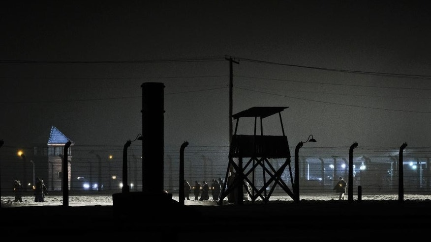 People walk holding lit candles past guard towers next to the railway leading to the Birkenau Nazi death camp in Oswiecim, Poland, Tuesday, Jan. 27, 2015, after the official remembrance ceremony. About 300 survivors gathered with leaders from around the world to remember the 1.1 million people killed at Auschwitz-Birkenau and the millions of others killed in the Holocaust.(AP Photo/Alik Keplicz)