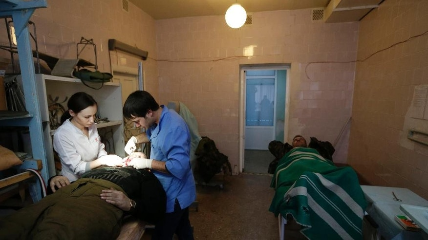 An injured Ukrainian soldier receives medical care at a hospital in the town of Artemivsk, Ukraine, Thursday, Jan. 29, 2015. Fighting between government and Russian-backed separatist forces in eastern Ukraine has intensified in recent days as rebels seek to encircle the town of Debaltseve, which hosts a strategically important railway hub. (AP Photo/Petr David Josek)