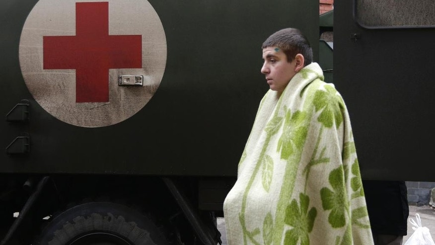 An injured Ukrainian soldier arrives at a hospital in the town of Artemivsk, Ukraine, Thursday, Jan. 29, 2015. Fighting between government and Russian-backed separatist forces in eastern Ukraine has intensified in recent days as rebels seek to encircle the town of Debaltseve, which hosts a strategically important railway hub. (AP Photo/Petr David Josek)