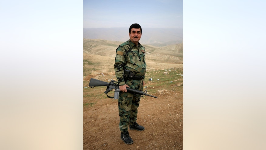 In this Thursday Jan. 29, 2015 photo, a Kurdish peshmerga soldier poses with a weapon on a hill near the town of Sinjar northern Iraq. Kurdish forces in recent weeks have retaken parts of the strategic Iraqi town of Sinjar, whose Yazidi population was driven out in a humanitarian disaster last year that triggered U.S. intervention. But disagreements among Kurdish factions makes the hold on the town seem shaky and is threatening the wider fight against Islamic state militants. (AP Photo/Bram Janssen)