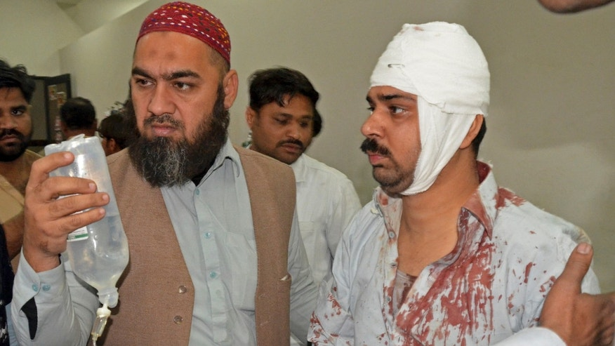 Jan. 30, 2015 - People help a person injured in a bomb blast as he arrives at a local hospital in Shikarpur, Pakistan. A bomb ripped through a mosque in Pakistan belonging to members of the Shiite minority sect of Islam just as worshippers were gathering for Friday prayers, killing dozens of people and wounding many others, officials said.