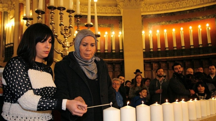 "FILE - This Sunday, Jan. 11, 2015, file photo shows Latifa Ibn Ziaten, 2nd left, mother of French soldier Imad Ibn Ziaten who was killed by Islamist gunman Mohamed Merah, attending a ceremony at the Grand Synagogue in Paris, France, for all the victims of the attacks in Paris this week, which claimed 17 lives. Latifa Ibn Ziaten knows the depth of the fracture between mainstream France and youth who grew up on the margins of society. She has been trying to heal it with a human touch, visiting schools and prisons for minors. Her work was triggered by the anguish of a mother trying to understand the real identity of her son's killer, and after she confronted youth from Merah's neighborhood _ who praised him as a ""hero of Islam."" For her, it felt as if her son was killed a second time _ until she discovered that ""these young people were completely lost."" (AP Photo/Matthieu Alexandre, Pool,  File)"