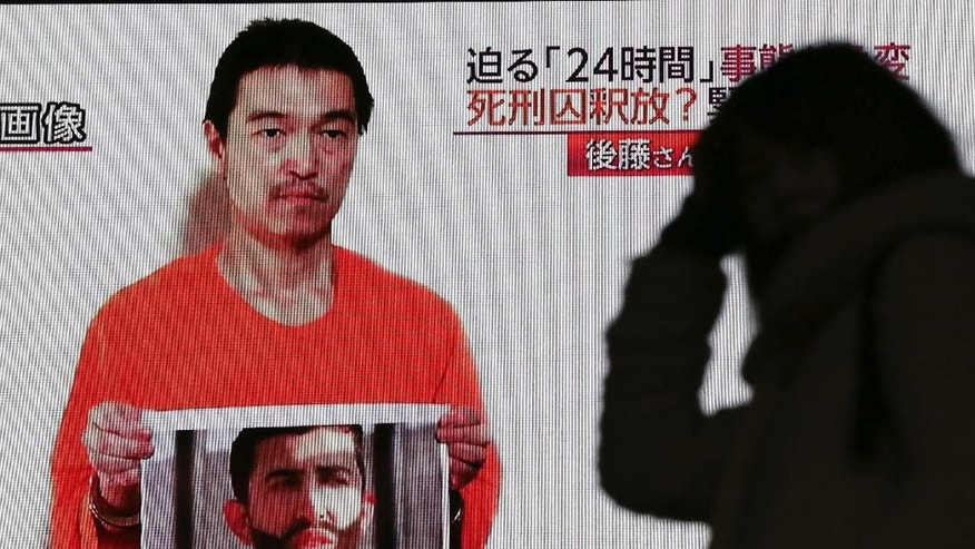 FILE - In this Wednesday, Jan. 28, 2015 file photo, a passerby is silhouetted against a large TV screen broadcasting a news program in Tokyo reporting on a video posted on YouTube by jihadists on Tuesday, Jan. 27, that purports to show a still photo of Japanese hostage Kenji Goto holding what appears to be a photo of Jordanian pilot 1st Lt. Mu'ath al-Kaseasbeh. Far from the high-tech, slickly edited videos involving beheaded Western hostages through which the group impressed supporters and terrorized opponents, recent messages purporting to be from Japanese hostage Kenji Goto have been through digitized, audio dispatches featuring either still photos or text. (AP Photo/Eugene Hoshiko, File)