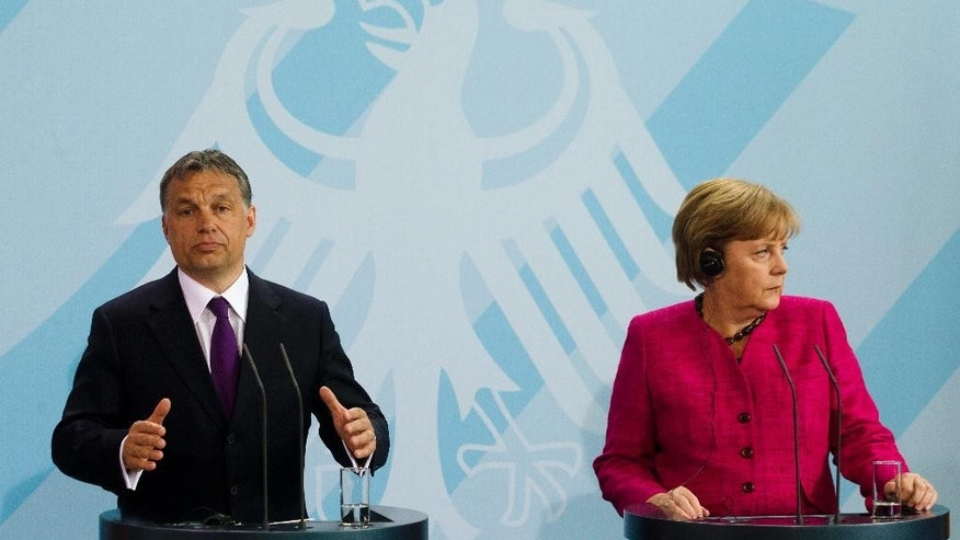 FILE - In this May 5, 2011 file photo German Chancellor Angela Merkel, right, and Hungarian Prime Minister Viktor Orban attend a news conference after a meeting at the chancellery in Berlin. Merkel is traveling to Budapest next week for talks with Hungarian Prime Minister Viktor Orban that come at a time of strain between the two nations, with Orban moving closer to Russia and imposing higher taxes and other burdens on German and other foreign companies operating in the country. (AP Photo/Markus Schreiber, file)