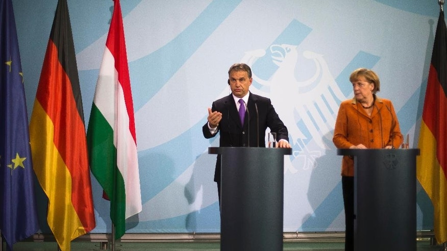 FILE - In this Oct. 11, 2012 file photo German Chancellor Angela Merkel, right, and Hungarian Prime Minister Viktor Orban brief the media after talks at the chancellery in Berlin. Merkel is traveling to Budapest next week for talks with Hungarian Prime Minister Viktor Orban that come at a time of strain between the two nations, with Orban moving closer to Russia and imposing higher taxes and other burdens on German and other foreign companies operating in the country.  (AP Photo/Markus Schreiber, file)