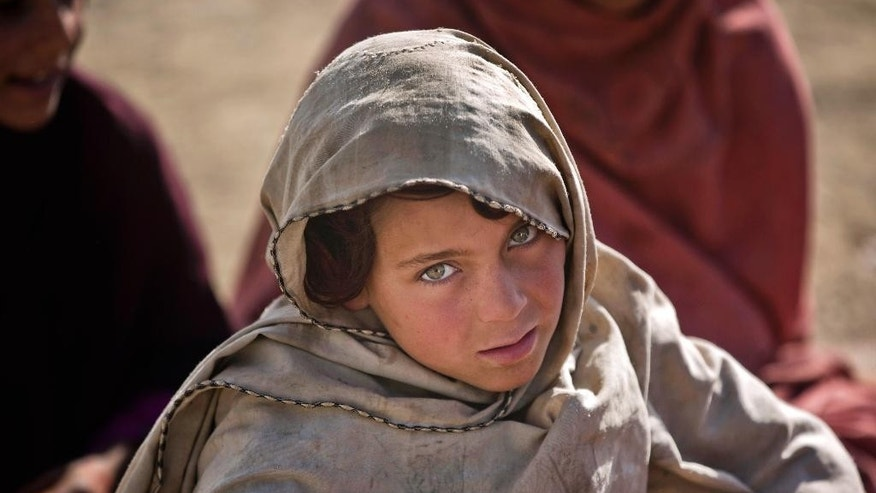 In this Monday, Jan. 19, 2015 photo, a Pakistani refugee schoolgirl attends class at Gulan camp, some 20 kilometers (12 miles) from the border in the restive Khost province, Afghanistan. For decades Afghans have fled into Pakistan to escape war and upheaval, but in recent months the tide has reversed, with some 60,000 Pakistanis - more than half of them children - taking refuge in the Gulan camp. (AP Photo/Massoud Hossaini)
