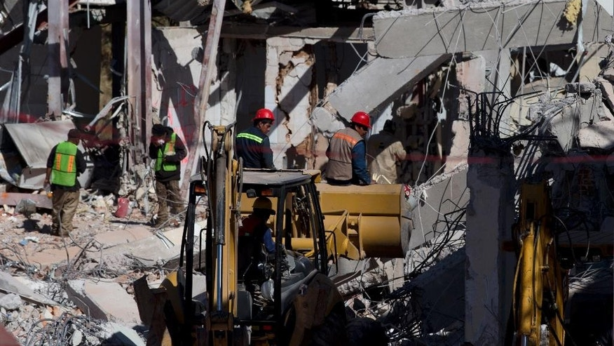 Workers continue to remove rubble, a day after a gas tank truck exploded outside a maternity hospital, causing most of the building to collapse, in Cuajimalpa on the western edge of Mexico City, Friday, Jan. 30, 2015. The blast occurred Thursday morning, when the truck was making a routine delivery of gas to the hospital kitchen and gas started to leak. Witnesses said the tanker workers struggled to repair the leak while a large cloud of gas formed. (AP Photo/Rebecca Blackwell)