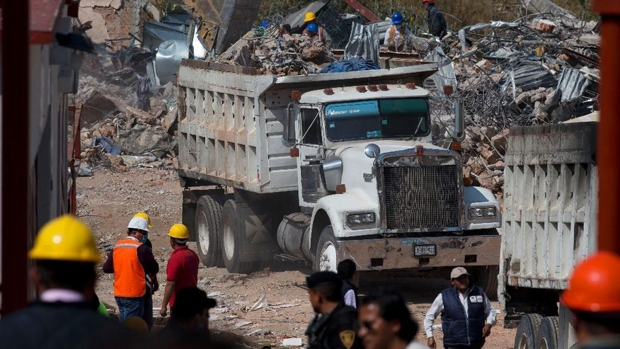 Dump trucks haul away loads of rubble, a day after a gas tank truck exploded outside a maternity hospital causing most of the building to collapse, in Cuajimalpa on the western edge of Mexico City, Friday, Jan. 30, 2015. The blast occurred Thursday morning, when the truck was making a routine delivery of gas to the hospital kitchen and gas started to leak. Witnesses said the tanker workers struggled to repair the leak while a large cloud of gas formed. (AP Photo/Rebecca Blackwell)