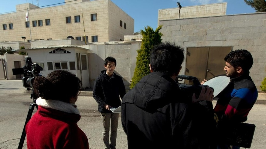 A Japanese television crew reports the news of a Jordanian and a Japanese citizen held by Islamic State group militants, in front of the Japanese embassy, in Amman, Jordan, Friday, Jan. 30, 2015. The fates of a Japanese journalist and Jordanian military pilot were unknown Friday, a day after the latest purported deadline for a possible prisoner swap passed with no further word from the Islamic State group holding them captive. (AP Photo/Nasser Nasser)