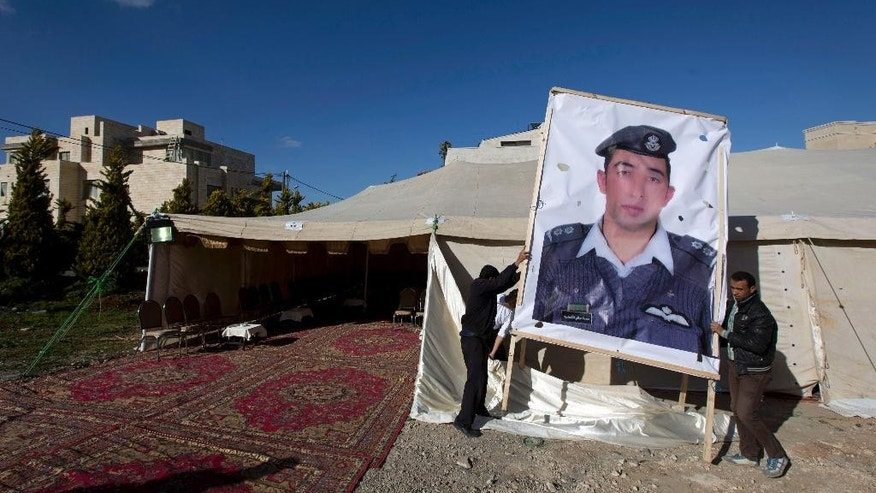 A banner with a picture of Jordanian pilot, Lt. Muath al-Kaseasbeh, who is held by Islamic State group militants, is hoisted by workers near a tent prepared for receiving supporters, in Amman, Jordan, Friday, Jan. 30, 2015. The fates of a Japanese journalist and Jordanian military pilot were unknown Friday, a day after the latest purported deadline for a possible prisoner swap passed with no further word from the Islamic State group holding them captive. (AP Photo/Nasser Nasser)
