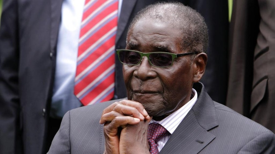 FILE - In this Friday, Dec, 12, 2014 file photo, Zimbabwean President Robert Mugabe sits after a swearing-in ceremony at State House in Harare, Zimbabwe. African leaders on Friday, Jan. 30, 2015 appointed 90-year-old Zimbabwean President Robert Mugabe, who has ruled his country since 1980, as the new chairman of the 54-nation African Union, succeeding Mauritania's President Mohamed Ould Abdel Aziz. (AP Photo/Tsvangirayi Mukwazhi, File)