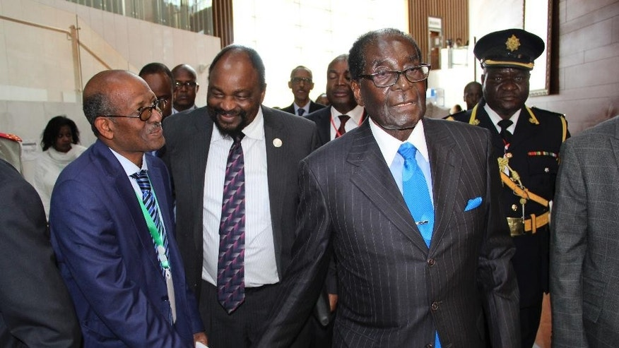 Zimbabwe's President Robert Mugabe, center-right, arrives for the heads of state meeting of the annual African Union (AU) summit, held at the AU headquarters in Addis Ababa, Ethiopia Friday, Jan. 30, 2015. African leaders Friday appointed 90-year-old Zimbabwean President Robert Mugabe, who has ruled his country since 1980, as the new chairman of the 54-nation African Union, succeeding Mauritania's President Mohamed Ould Abdel Aziz. (AP Photo)