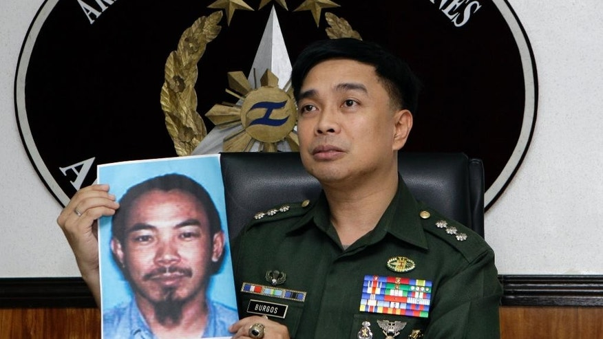 FILE - In this Feb. 2, 2012 file photo, then Armed Forces of the Philippines spokesman Col. Marcelo Burgos shows a picture of Malaysian Zulkifli bin Hir, also known as Marwan, during a press conference in suburban Quezon City, north of Manila, Philippines. Southeast Asia's top terrorist suspect has evaded capture and survived several military assaults in the southern Philippines, where police now await DNA results to confirm if he is the man killed in the Jan. 25, 2015 raid that also left 44 police commandos dead.  (AP Photo/Pat Roque, File)