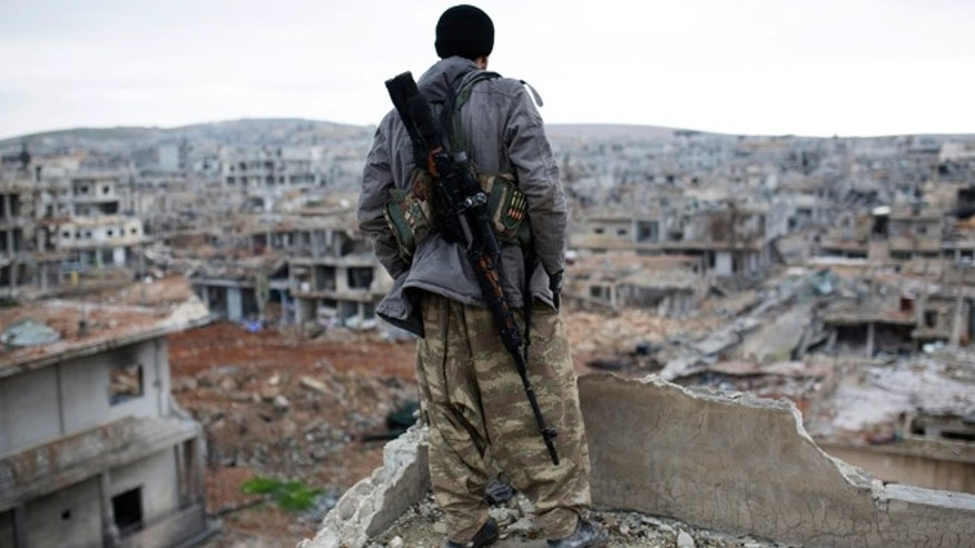 Jan. 30, 2015: A Syrian Kurdish sniper looks at the rubble in the Syrian city of Ain al-Arab, also known as Kobani. (AP)