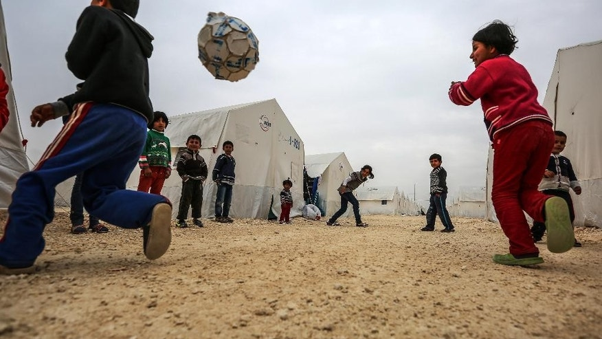 Syrian refugee children who fled violence in Syrian city of Ayn al-Arab or Kobani play outside their tent in Turkey's newly set-up camp in the border town of Suruc, Turkey, Friday, Jan. 30, 2015. The 35,000 people capacity camp is the biggest refugee camp in Turkey. About 200,000 people arrived in Turkey since the start of fighting between Kurdish militia and Islamic State militants mid-September, 2014. (AP Photo/Emrah Gurel)