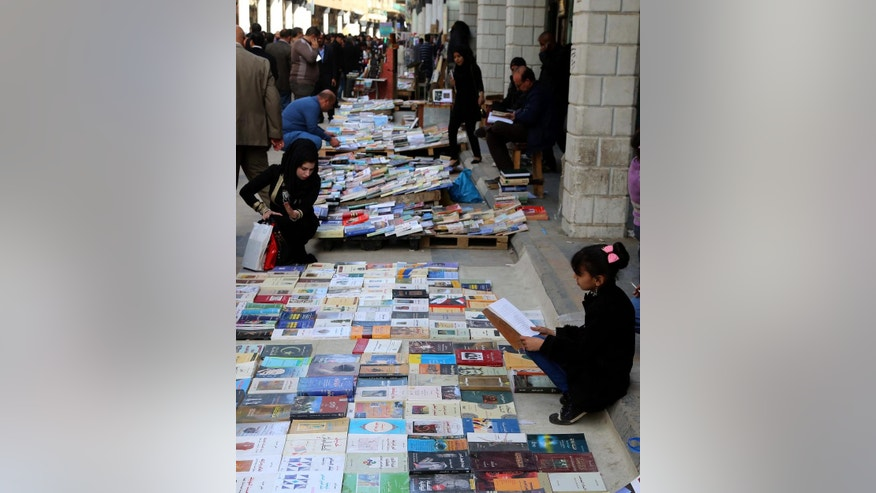 In this Friday, Jan. 23, 2015 photo, Iraqis look at books on al-Mutanabi Street, home to the city's book market in central Baghdad. One afternoon this month, the Islamic State militants arrived at the Central Library of the northern city of Mosul in a non-combat mission. They broke the locks that kept the two-story building closed since the extremists overran the city in mid last year, loading some 2,000 books included children stories, poetry, philosophy, sports, health and cultural and scientific publications into six pickup trucks and leaving behind only the Islamic religious ones. (AP Photo/Karim Kadim)