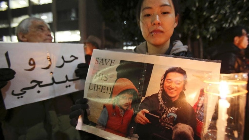 FILE - In this Friday, Jan. 30, 2015 file photo, a protester holding a photo of Japanese journalist Kenji Goto who was taken hostage by the Islamic State group appeals to the government to save Goto during a rally in front of  the prime minister's official residence in Tokyo. Whether in tsunami-stricken northeastern Japan or conflict-ridden Sierra Leone, it was the story of the vulnerable, the children and the poor that drove the work of Goto. The news of his killing in a video purportedly by Islamic State militants sent Japan into shock and mourning Sunday, Feb. 1, days after his plight as a hostage in Syria united many people in praying for his release. (AP Photo/Koji Sasahara, File)