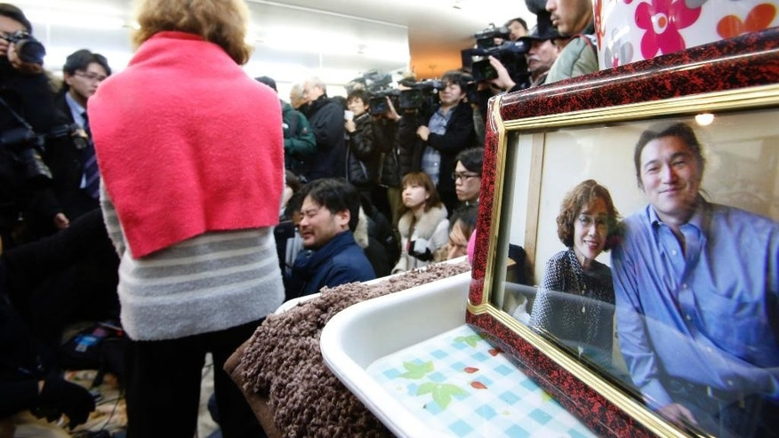 FILE - In this Friday, Jan. 30, 2015 file photo, Junko Ishido, the mother of Japanese journalist Kenji Goto who was taken hostage by the Islamic State group, speaks to the media during a press conference as a framed photo of her with Goto is displayed at her home in Koganei on the outskirts of Tokyo. Whether in tsunami-stricken northeastern Japan or conflict-ridden Sierra Leone, it was the story of the vulnerable, the children and the poor that drove the work of Goto. The news of his killing in a video purportedly by Islamic State militants sent Japan into shock and mourning Sunday, Feb. 1, days after his plight as a hostage in Syria united many people in praying for his release. (AP Photo/Shizuo Kambayashi, File)