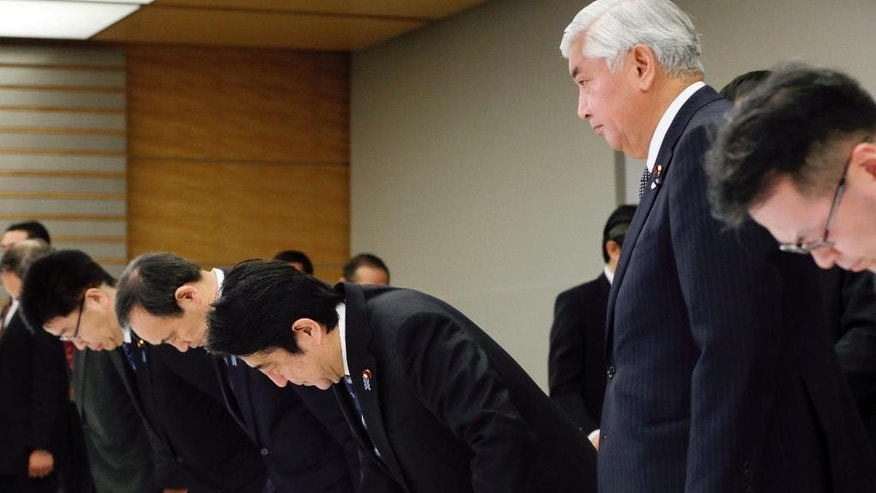 Japanese Prime Minister Shinzo Abe, third right, bows as he attends a ministerial meeting at the prime minister's official residence in Tokyo, Sunday, Feb. 1, 2015 after the release of an online video that purported to show an Islamic State group militant beheading Japanese journalist Kenji Goto. Japan condemned with outrage and horror on Sunday the video posted on militant websites late Saturday Middle East time. Defense Minister Gen Nakatani, second right, and Chief Cabinet Secretary Yoshihide Suga, fourth right, also attend the meeting. (AP Photo/Kimimasa Mayama, Pool)