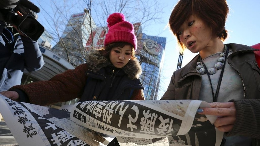 "Japanese women react as they read extra newspapers in Tokyo reporting about an online video that purported to show an Islamic State group militant beheading Japanese journalist Kenji Goto, Sunday morning, Feb. 1, 2015. Japan condemned with outrage and horror on Sunday after the video was posted on militant websites late Saturday Middle East time. The headline reads: ""A video on killing of Goto."" (AP Photo/Eugene Hoshiko)"