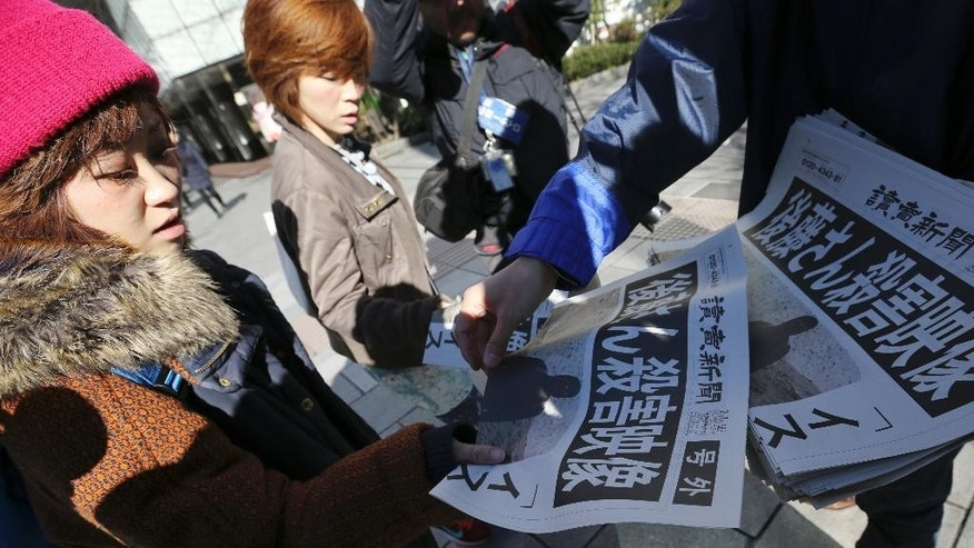 "Passersby react as they receive extra newspapers in Tokyo reporting about an online video that purported to show an Islamic State group militant beheading Japanese journalist Kenji Goto,  Sunday morning, Feb. 1, 2015. Japan condemned with outrage and horror on Sunday after the video was posted on militant websites late Saturday Middle East time. The headline reads: ""A video on killing of Goto."" (AP Photo/Eugene Hoshiko)"