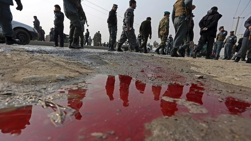 Afghan police are reflected in blood from injured protestors mixed water at the scene of a protest against caricatures of the Prophet Muhammad published in the French magazine Charlie Hebdo, in Kabul, Afghanistan, Saturday, Jan. 31, 2015. Hundreds of people demonstrated in the Afghan capital accusing the French satirical magazine of blasphemy. (AP Photo/Rahmat Gul)