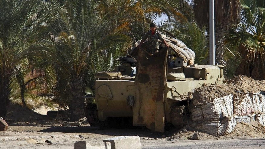 An Egyptian soldier stands on armored vehicle in el-Arish, 290 kilometers (180 miles) east of Cairo, North Sinai, Egypt, Saturday, Jan. 31, 2015. Egyptian President Abdel Fattah al-Sissi told the nation in a televised address Saturday to prepare for a long fight to defeat Islamic extremists following a wave of attacks on security forces in the Sinai Peninsula. An Islamic State-linked group in Egypt claimed responsibility for a string of bomb and gun attacks Thursday night targeting Egyptian military positions that killed at least 30 security force members. (AP Photo)
