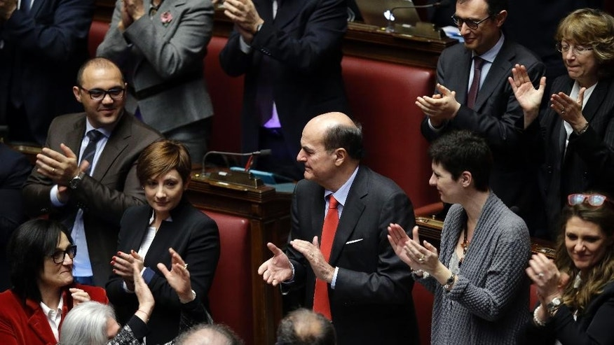 Center-left lawmaker Pierluigi Bersani, center, applauds the election of Italy's new President Sergio Mattarella, at the end of a voting session for the election of the new Italian President, at the lower chamber, in Rome, Saturday, Jan. 31, 2015. Italian lawmakers have elected Constitutional Court justice Sergio Mattarella on the third day of voting. Mattarella's victory was clinched Saturday when he amassed 505 votes — a simple majority — with the count incomplete. Renzi had pushed hard for Mattarella's election, and some of Renzi's rebellious Democrats had protested that the premier had imposed his choice on them. Mattarella, 73, with Christian Democrat roots, is considered to be above the political fray. (AP Photo/Andrew Medichini)