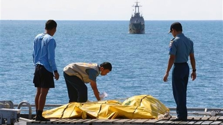 Crew members inspect bags containing bodies believed to be victims of AirAsia Flight 8501 on the deck of Indonesian Navy ship KRI Banda Aceh, on the Java Sea, Indonesia, Friday, Jan. 23, 2015. The ill-fated jetliner plunged into the java Sea while en route from Surabaya, Indonesia's second-largest city, to Singapore last month. (AP Photo/Natanael Pohan)
