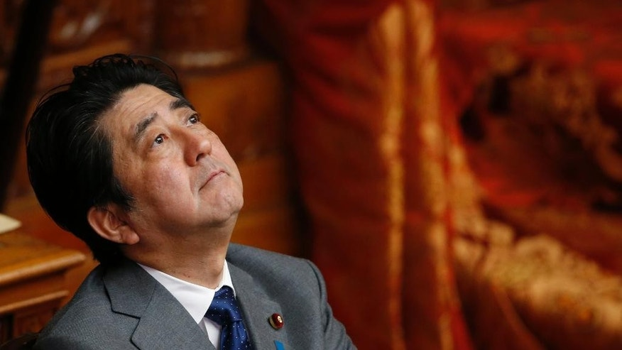 In this Wednesday, Jan. 28, 2015 photo, Japan's Prime Minister Shinzo Abe looks up during a Diet session at the upper house of Parliament in Tokyo as his government is working closely with Jordan to save a Japanese hostage taken by the Islamic State group. The Japanese, who inhabit one of the safest countries in the world, have been reminded in brutal fashion that the world is a dangerous place. In a shock to a country that can feel insulated from distant geopolitical problems, two of their own have reportedly been killed by Islamic radicals in Syria, the latest apparently beheaded in a video posted online this weekend by militant websites. Abe, in a bid to restore Japan's position in the world, has been driving his country to play a larger international role, most controversially seeking to loosen constitutional restraints put on its military after World War II.  (AP Photo/Shizuo Kambayashi)
