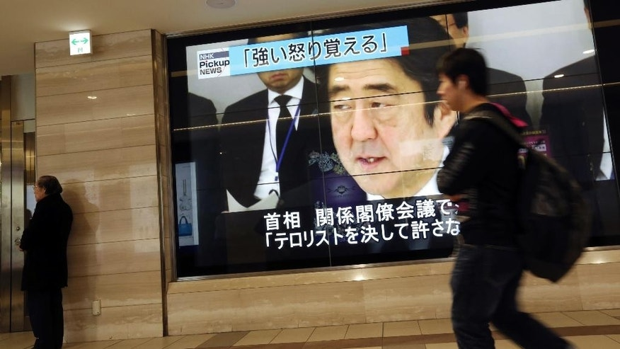 "A man walks past a screen in Tokyo Sunday, Feb. 1, 2015 showing TV news reports of Japanese Prime Minister Shinzo Abe talking at an emergency Cabinet meeting, 2015 after the release of an online video that purported to show an Islamic State group militant beheading Japanese journalist Kenji Goto. This island nation, which once closed itself to the outside world for two centuries under samurai rule, has been venturing out as it has in fits and starts for the past two decades. Abe, in a bid to restore Japan's position in the world, has been driving his country to play a larger international role, most controversially seeking to loosen constitutional restraints put on its military after World War II.  Japanese shown on the top of the screen reads: ""I feel indignation."" (AP Photo/Eugene Hoshiko)"