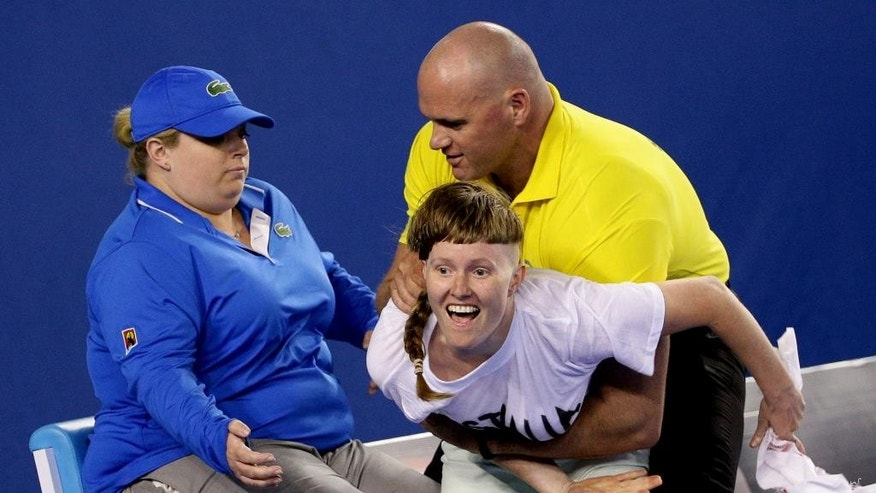 A political protester, center,  is caught by a security guard during the men's singles final between Andy Murray of Britain and Novak Djokovic of Serbia at the Australian Open tennis championship in Melbourne, Australia, Sunday, Feb. 1, 2015. (AP Photo/Rob Griffith)