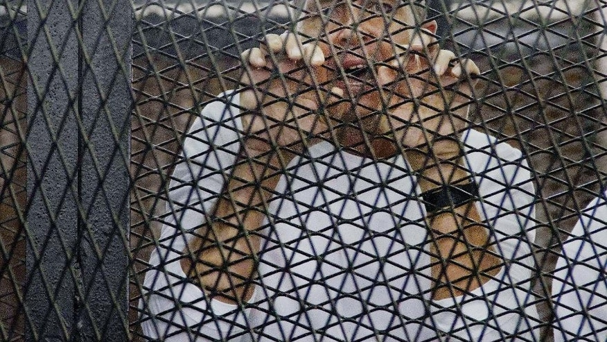 FILE - In this Saturday, May 3, 2014 file photo, Al-Jazeera's award-winning Australian correspondent Peter Greste, appears in a defendants' cage in a courthouse near Tora prison in Cairo, Egypt. A senior Egyptian prison official and the country's official news agency say Greste has been freed from prison and is on his way to Cairo airport to leave the country. (AP Photo/Hamada Elrasam, File)