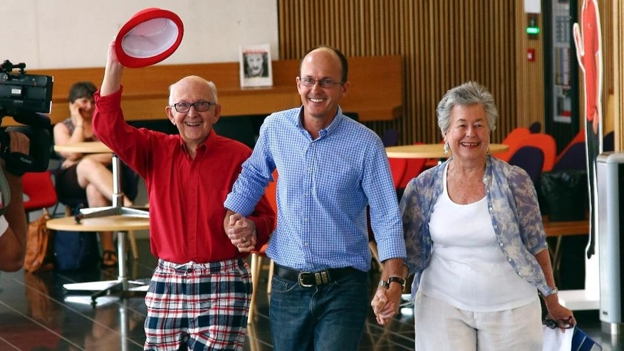 Juris, left, and Lois Greste, parents of Australian journalist Peter Greste, and his brother Andrew, center, arrive at a press conference in Brisbane, Australia, Monday, Feb. 2, 2015. Peter Greste, a reporter for Al-Jazeera English was released from an Egyptian prison and deported Sunday after more than a year behind bars.  (AP Photo/Tertius Pickard)