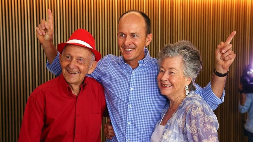 Juris, left, and Lois Greste, parents of Australian journalist Peter Greste, and his brother Andrew, center, pose for the media at a press conference in Brisbane, Australia, Monday, Feb. 2, 2015. Peter Greste, a reporter for Al-Jazeera English was released from an Egyptian prison and deported Sunday after more than a year behind bars. (AP Photo/Tertius Pickard)