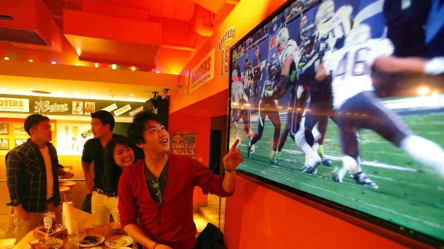 Japanese watch the replay of Super Bowl game played earlier in the day shown on a large screen at Hooters sports bar in Tokyo's Ginza district Monday evening, Feb. 2, 2015. In Tokyo, the start of the Super Bowl coincided with the Monday morning commute. That didn't stop a large group of hardcore Japanese football fans from taking time off work as a boisterous gathering of about 200 crammed into a Hooters sports bar in the Akasaka business district to catch the game. (AP Photo/Shizuo Kambayashi)