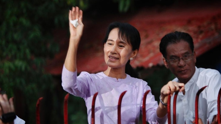 In this Nov. 13, 2010 photo, Myanmar's Aung San Suu Kyi, left behind the gate, addresses her supporters from her house compound after her release from house arrest in Yangon, Myanmar. The iron gate that stood in front of the home of Myanmar's formerly imprisoned democracy icon, separating her from throngs of cheering supporters as she made speeches challenging the country's then-military rulers, is going on the auction block. Soe Nyunt, the current owner, said Monday, Feb. 2, 2015 the starting bid would be $200,000. (AP Photo/Gemunu Amarasinghe)