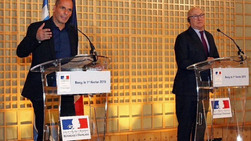 Greek finance minister Yanis Varoufakis, left, addresses reporters during a joint press conference with his French counterpart Michel Sapin, at the Economy Ministry in Paris, Sunday Feb. 1, 2015. Finance Minister Yanis Varoufakis, who had a tense meeting with Eurogroup leader Jeroen Dijsselbloem in Athens on Friday, has brought forward a trip to Paris, London and Rome to meet his counterparts. (AP Photo/Remy de la Mauviniere)