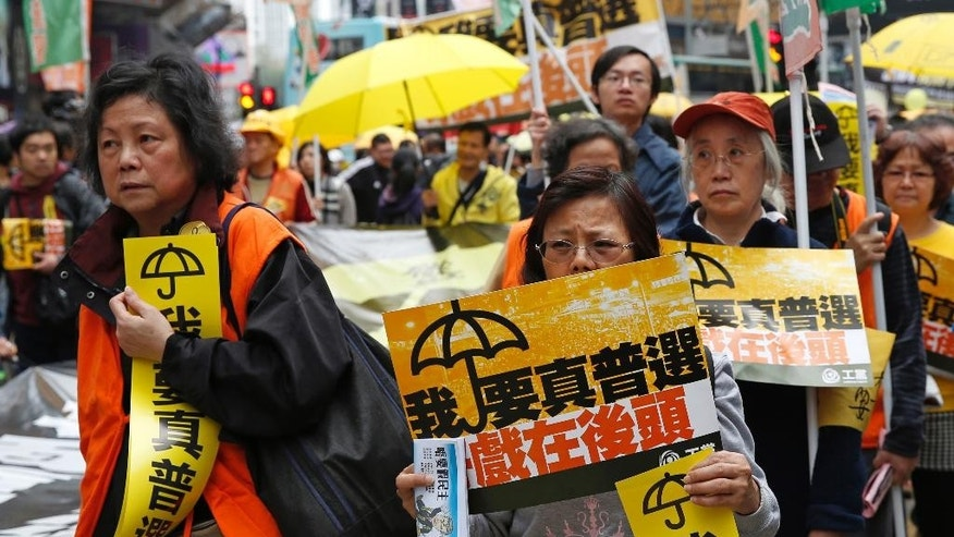 "Thousands of pro-democracy activists take part in a democracy march to Central, demanding for universal suffrage in Hong Kong Sunday, Feb. 1, 2015. The march is the first large-scale demonstration since the Occupy Central protest ended last year as the government started a second round of public consultation on democratic reform. The yellow placards read: ""I want genuine universal suffrage."" (AP Photo/Kin Cheung)"