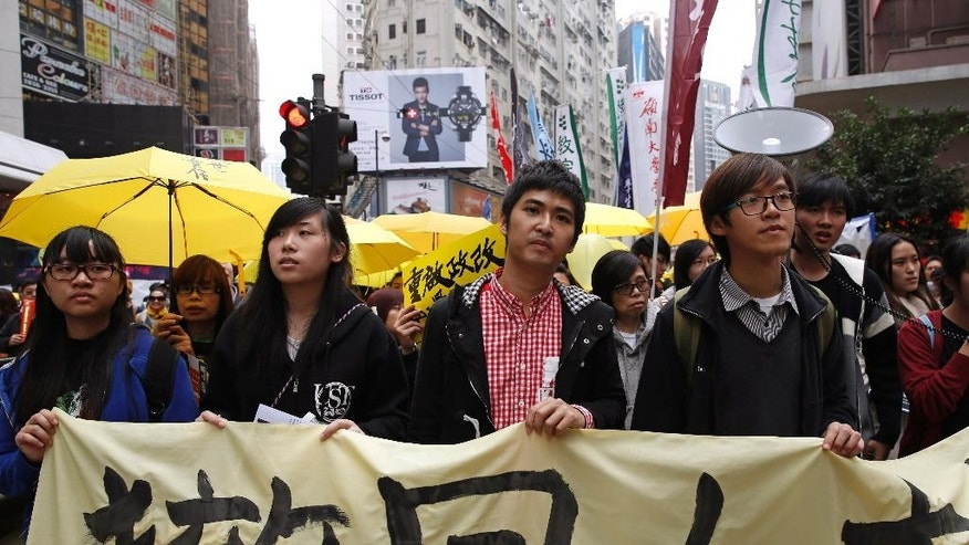 "Student leader Alex Chow, center, carries a banner with other students during a democracy march to Central, demanding for universal suffrage in Hong Kong Sunday, Feb. 1, 2015. The march is the first large-scale demonstration since the Occupy Central protest ended last year as the government started a second round of public consultation on democratic reform. The banner reads: ""Withdraw."" (AP Photo/Kin Cheung)"