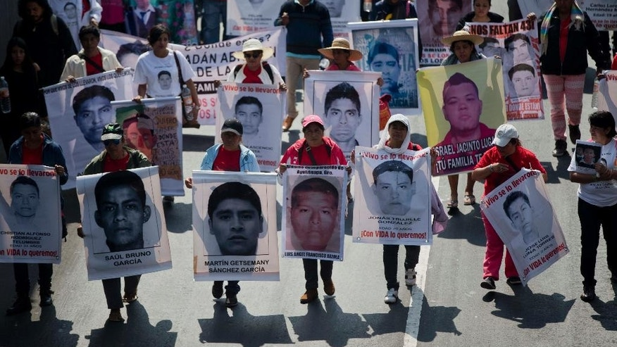 FILE - In this Jan. 26, 2015 file photo, relatives and protestors carry pictures of some of the 43 students who went missing in Sept. 26, 2014 from a rural teachers college in Guerrero state, during a march in Mexico City. Mexico has a serious problem with disappearances and lacks a comprehensive national list of the missing to effectively deal with the problem, according to a report the country's National Human Rights Commission will present Monday, Feb. 2, 2015 to the U.N. (AP Photo/Eduardo Verdugo, File)